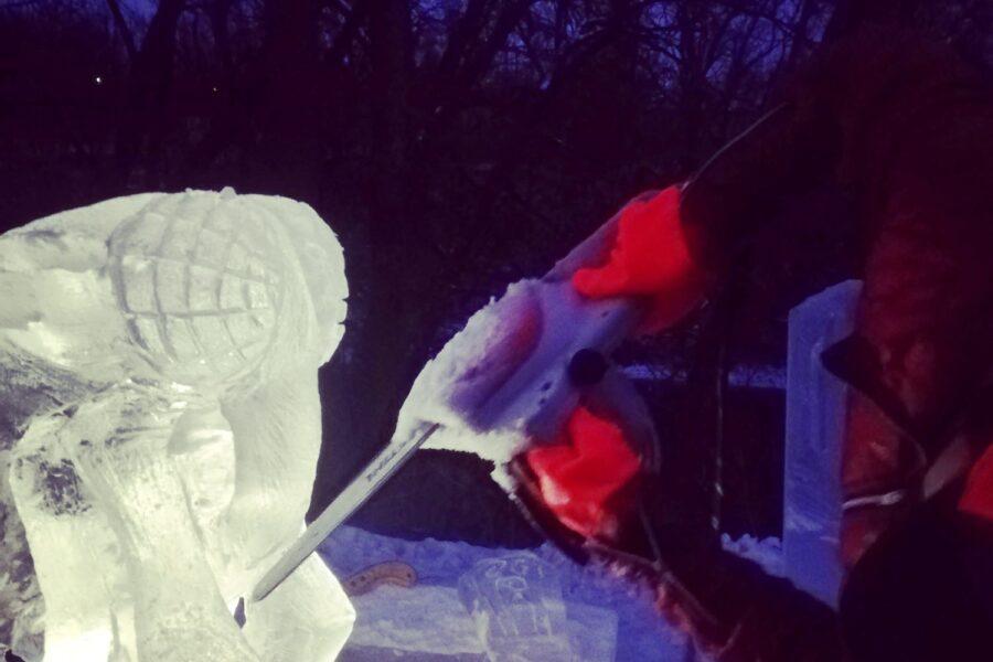 Un homme sculpte un bloc de glace avec une scie en hiver à la tombée du jour.